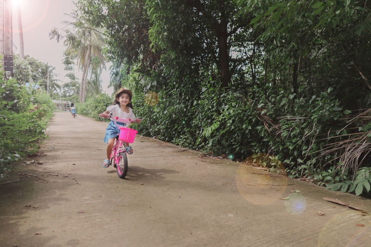 Girl riding bicycle on road amidst trees
