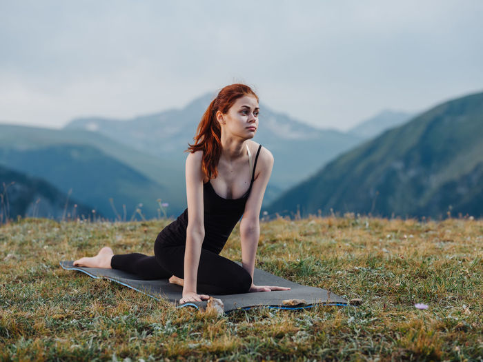 Woman with arms raised against mountains