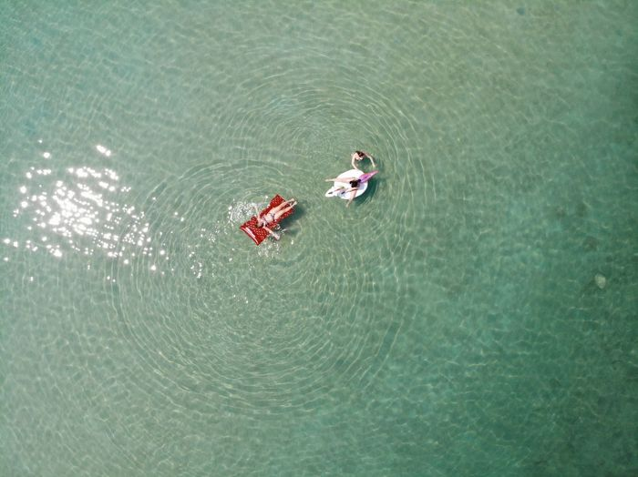 Red Swimming Unicorn Aerial View Air Mattress Beauty In Nature Day High Angle View Lake Leisure Activity Men Nature Outdoors People Real People Rippled Sea Swimming Trip Turquoise Colored Two People Two People Alone In Nature Vacations Water Waterfront