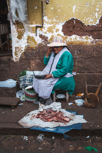 Exploring the street market just south of the San Pedro Market. Andes Backpacking City Cityscape Exploring Inca Latin America Traditional Clothing Casual Clothing Colonial Day Food And Drink Freshness Holding Lifestyles Meat People Preparation  Real People Sitting South America Telephone Travel Destinations Urban Women The Traveler - 2018 EyeEm Awards The Street Photographer - 2018 EyeEm Awards
