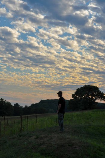 Silhouette of a Man in a Park Silhouette Beauty In Nature Cloud - Sky Dusk Field Full Length Landscape Leisure Activity Lifestyles Nature One Person Outdoors People Real People Scenics Sky Standing Sunset