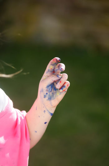 Cropped hand of girl with paint stains