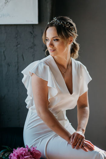 Beautiful woman sitting on floor against wall