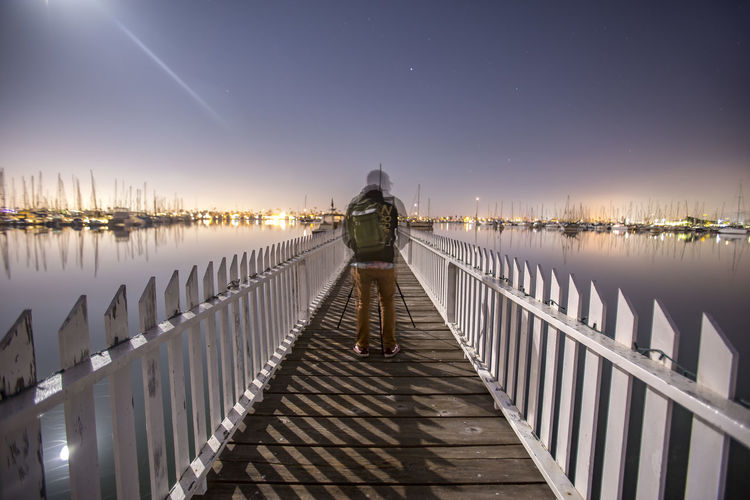 Rear view of man standing on footbridge over sea at night