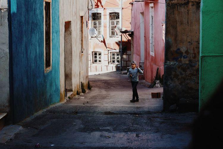 Man walking on footpath amidst buildings