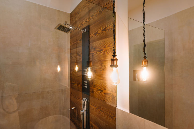 Illuminated lighting equipment hanging on ceiling in the bathroom at home