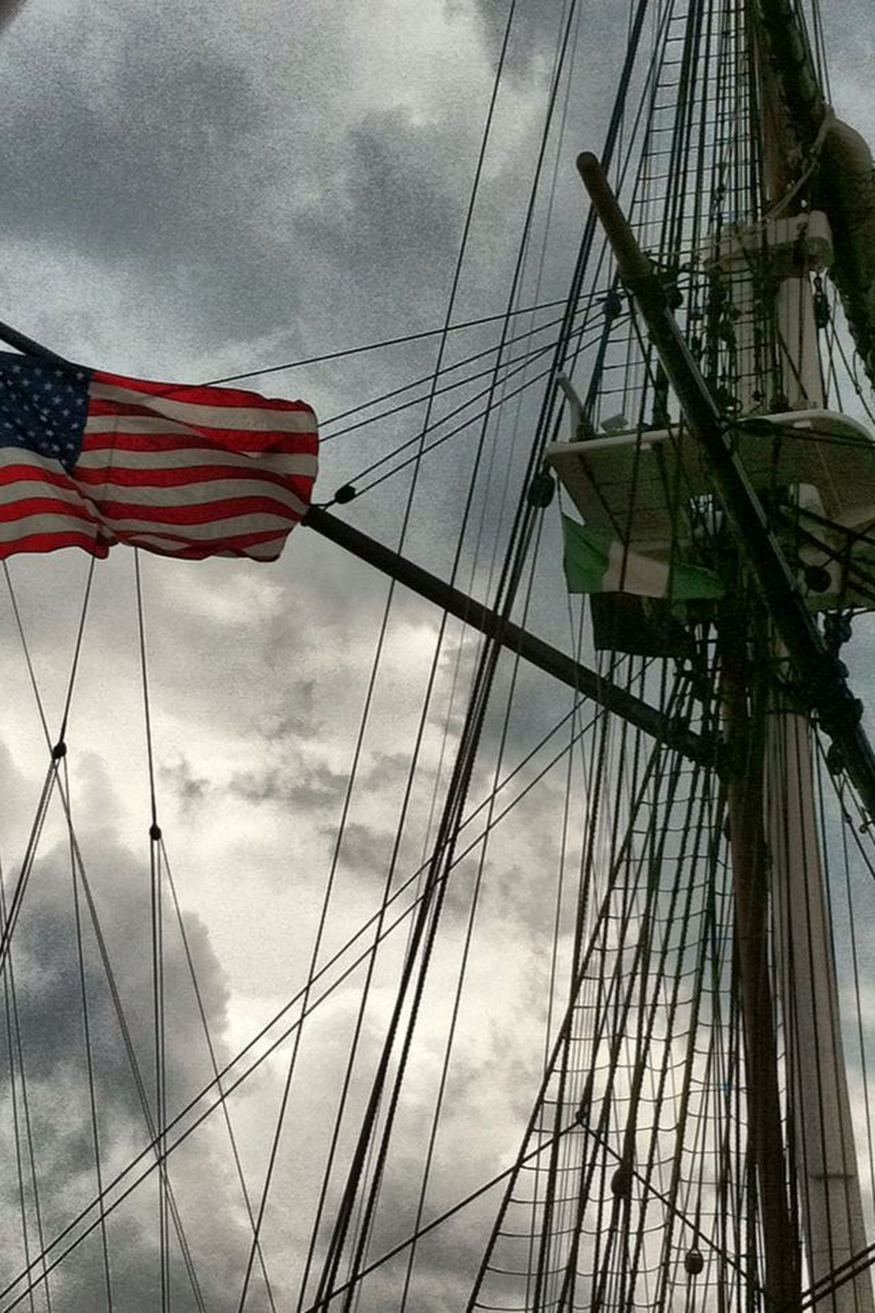 low angle view, sky, cloud - sky, flag, built structure, architecture, american flag, identity, cloudy, patriotism, building exterior, national flag, cloud, day, mast, wind, outdoors, rope, no people, nautical vessel