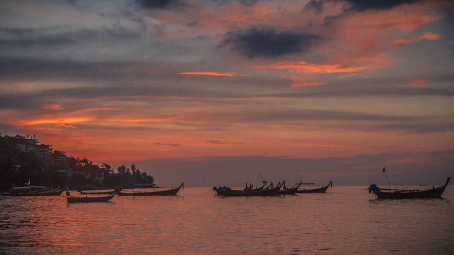 Silhouette of longtail boats moored on sea against sky during sunset