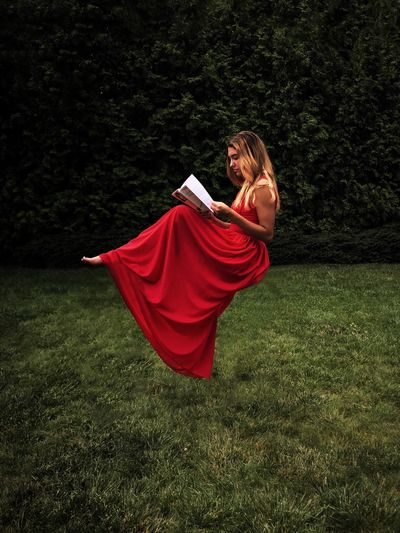 Side View Of Teenage Girl Reading Book While Levitating Over Grassy Field