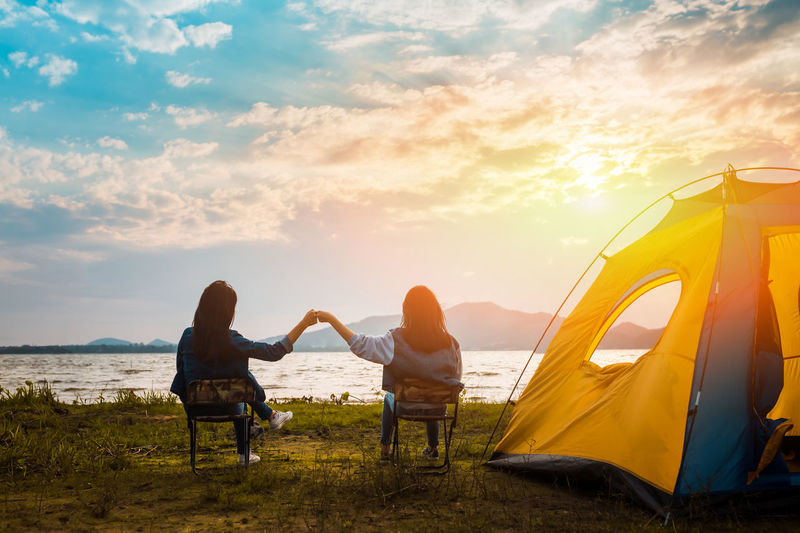 Friendship of young women resting camp near mountain after trekking destination together with tent at sunset. Sky Sunset Real People Cloud - Sky Leisure Activity Lifestyles Beauty In Nature Two People Adult Nature Water Land Sea Togetherness People Women Positive Emotion Beach Vacations Couple - Relationship Outdoors