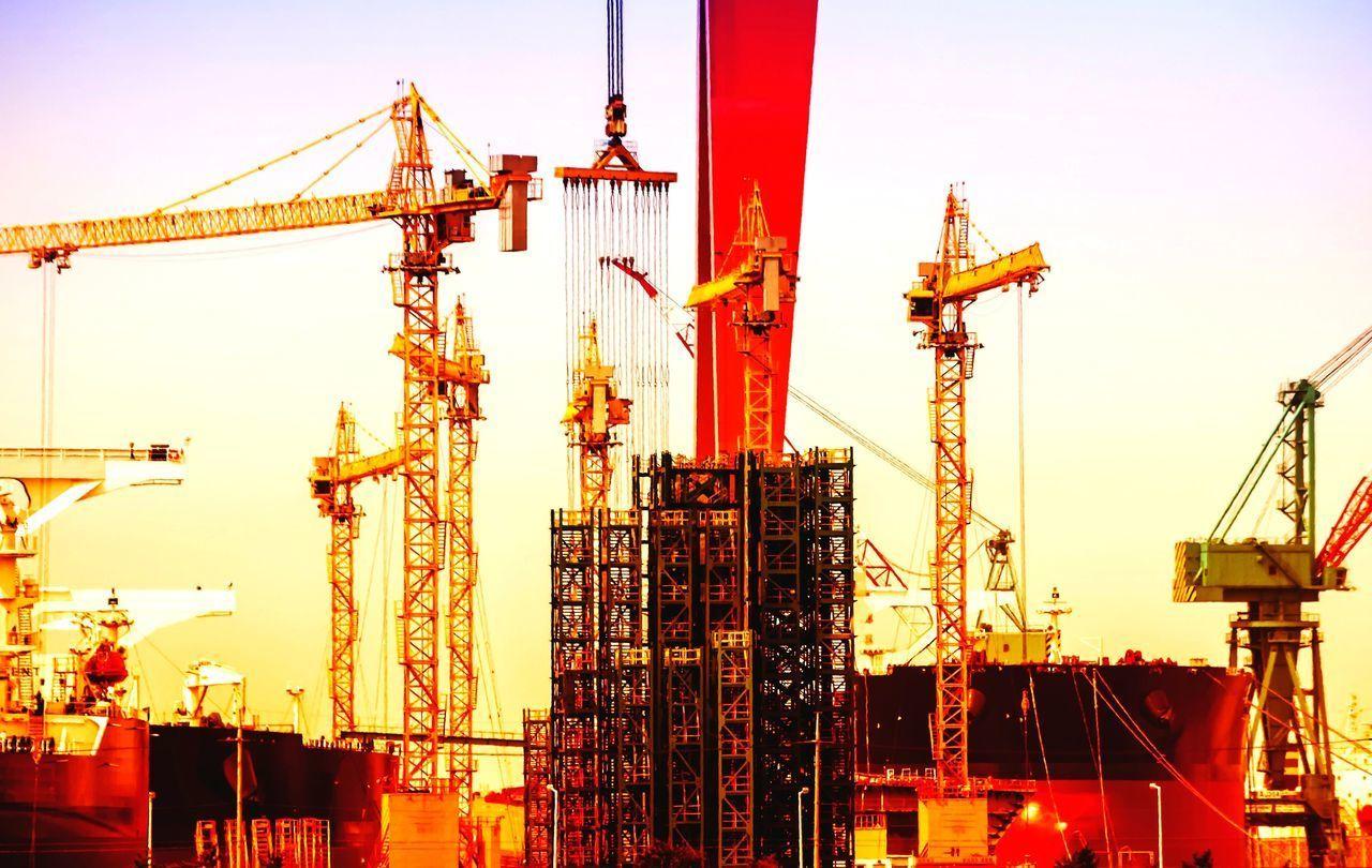 CRANE AT CONSTRUCTION SITE AGAINST SKY