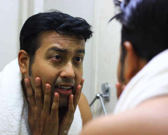 Man washing his face in mirror. Men styling. Face Wash Facewashing Shaving Mime Men Young Women Women Portrait Human Face Headshot Actor City Human Eye Mirror Facial Mask - Beauty Product Beauty Treatment Anti Aging Skin Care Exfoliation