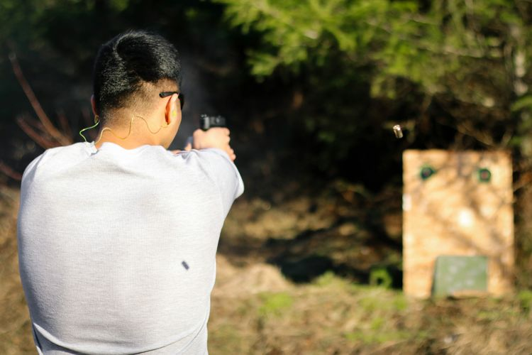 Rear View Of Man Shooting Target On Field