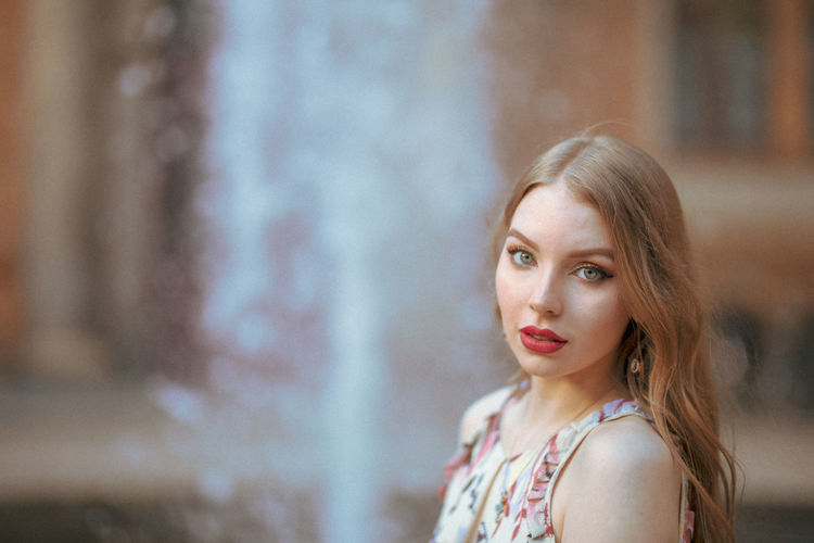 Portrait of beautiful young woman standing against fountain in city