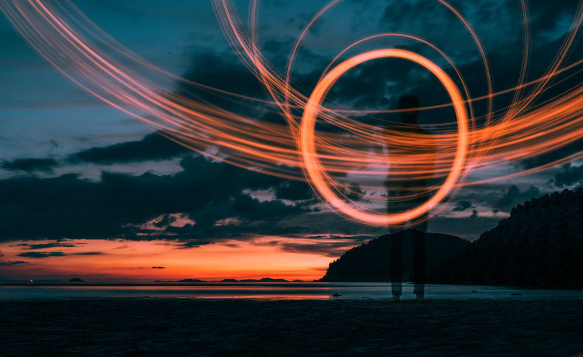 Man standing by light painting at beach during sunset