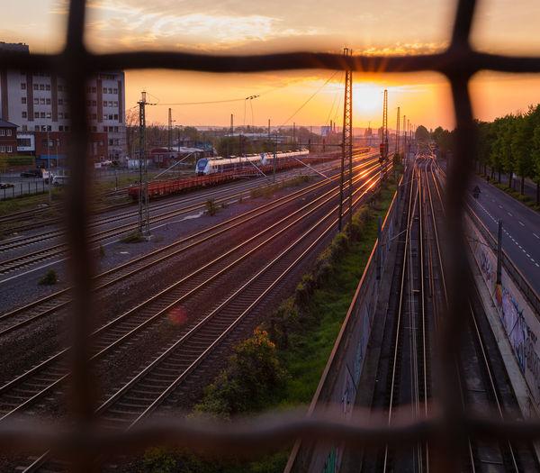 Railway tracks against sky at sunset