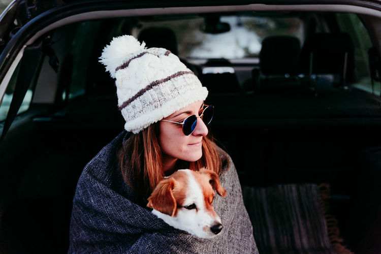 Close-up of woman with dog sitting in car trunk