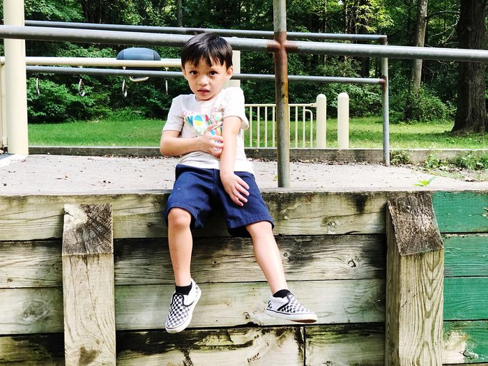 Boy sitting at the park Playground Park MidWest Asian  Mixed Race Full Length Childhood Child Casual Clothing Real People One Person Leisure Activity Front View Lifestyles Day Sitting Fence Innocence Boys Outdoors
