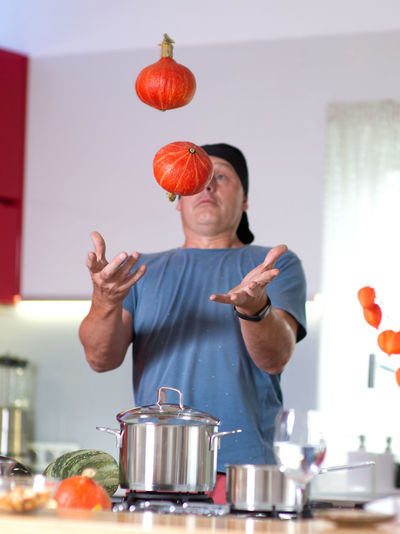Man playing with pumpkins while preparing food in kitchen
