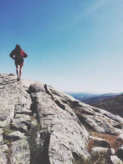 Rear view of a woman walking on rocky landscape