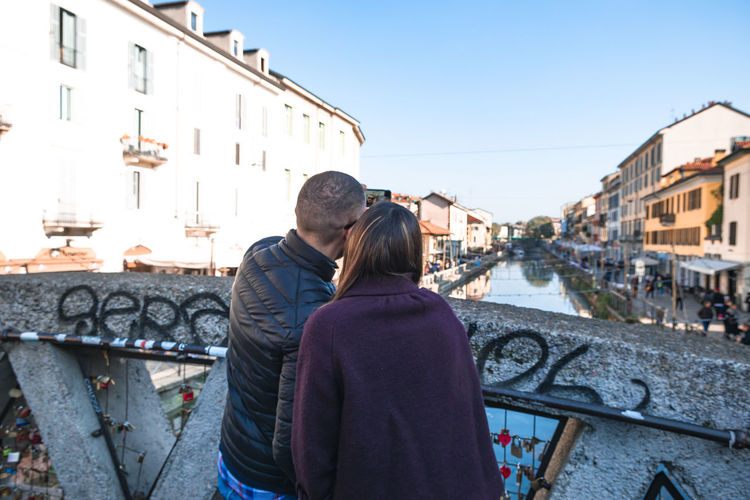 Rear view of couple standing on canal in city