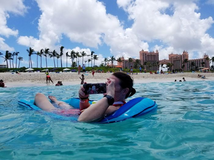 Man photographing through mobile phone while relaxing in sea against sky