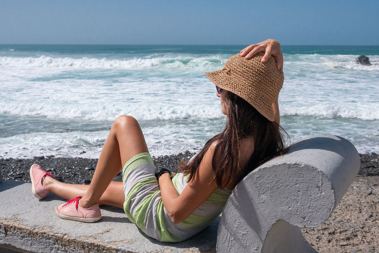 Sea Water Land One Person Leisure Activity Beach Sitting Relaxation Lifestyles Real People Hat Women Beauty In Nature Nature Adult Horizon Over Water Full Length Horizon Hair Outdoors Hairstyle Sun Hat