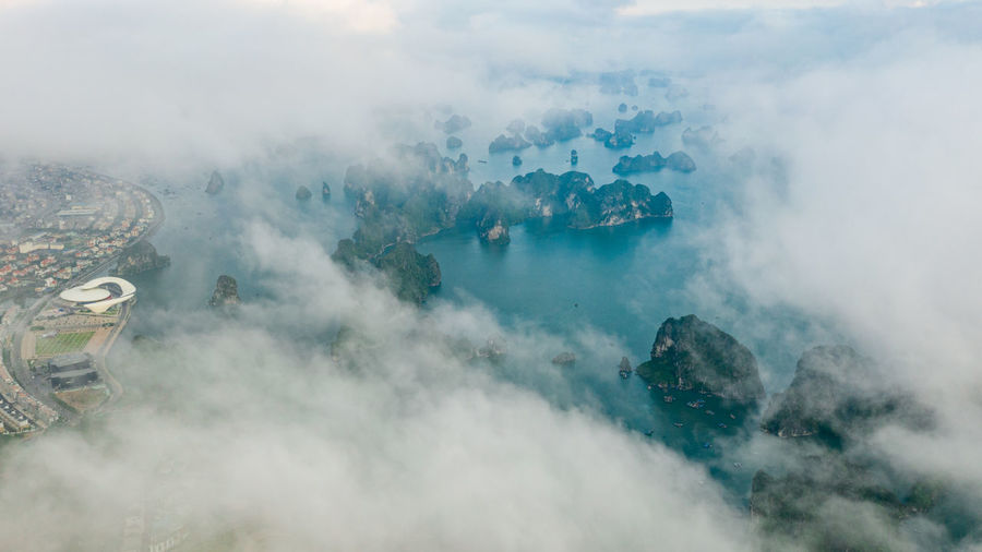 Aerial view of rock formations in sea seen through cloudy sky