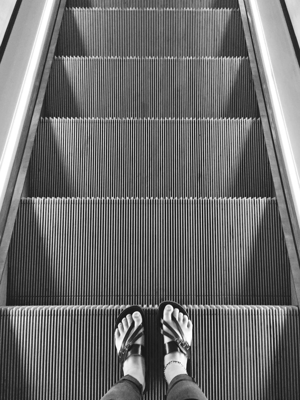 escalator, staircase, shoe, steps and staircases, steps, low section, standing, high angle view, human leg, modern, indoors, one person, metal, convenience, shiny, transportation, human body part, men, technology, futuristic, people, adults only, adult, day, one man only