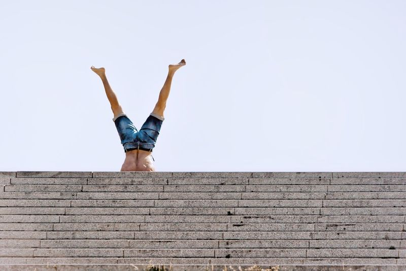 Upside down Stairs Human Legs One Person Sky Architecture Wall - Building Feature Day Lifestyles The Street Photographer - 2018 EyeEm Awards Real People Built Structure Casual Clothing Full Length Low Angle View Young Adult Upside Down Balance Leisure Activity Outdoors