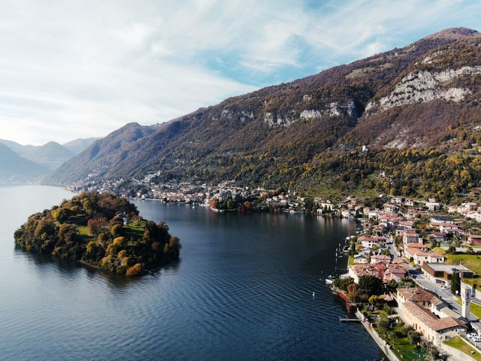 Scenic view of como lake townscape by mountains against sky
