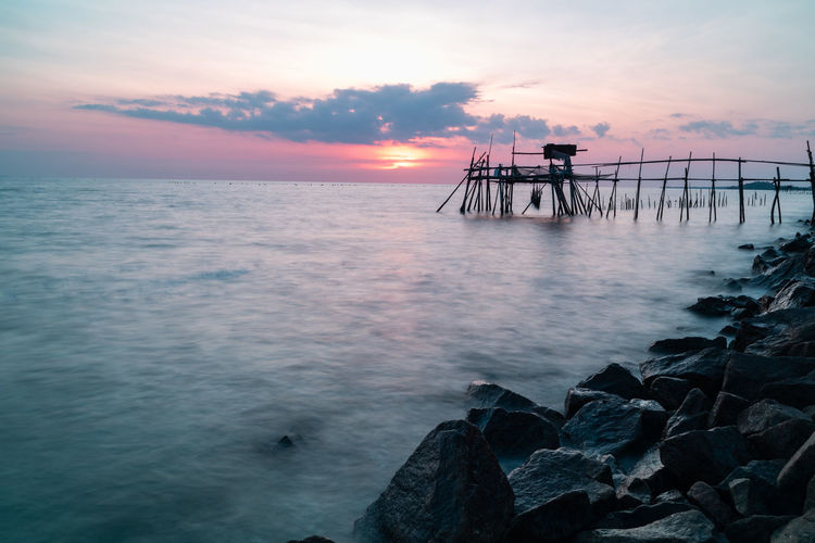 Wooden jetty at the rocky seaside during sunset. Sky Sea Sunset Water Beauty In Nature Scenics - Nature Horizon Over Water Tranquil Scene Rock Cloud - Sky Horizon Tranquility Rock - Object Idyllic Solid Nature Orange Color Real People Non-urban Scene Outdoors Sun Long Exposure Seascape Colors Calm