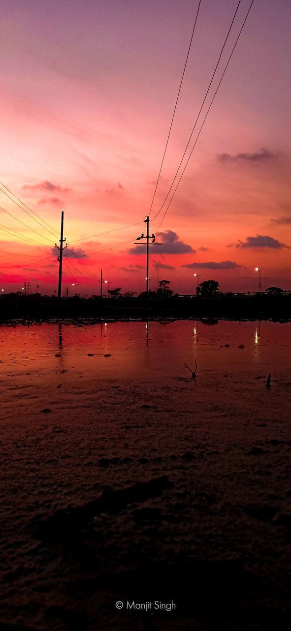SILHOUETTE ELECTRICITY PYLONS AGAINST ORANGE SKY
