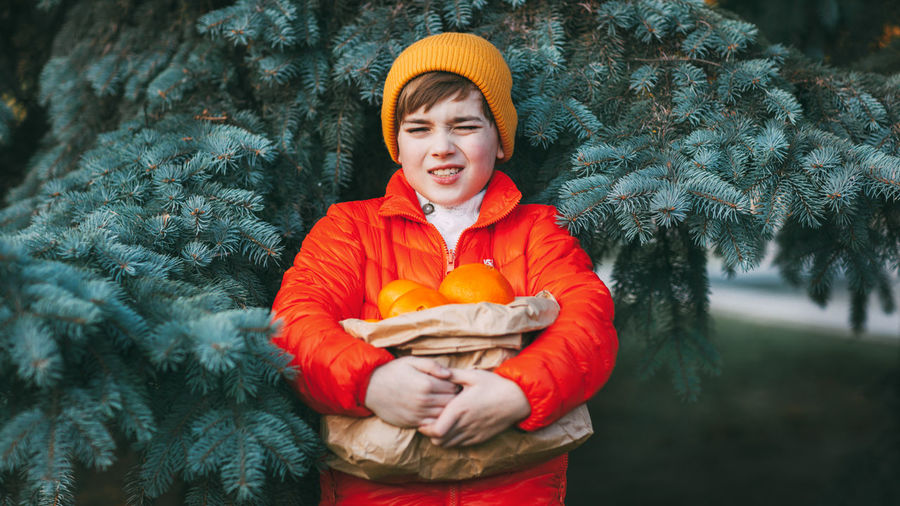 A cute boy in a bright orange jacket and a yellow hat holds a large package with oranges
