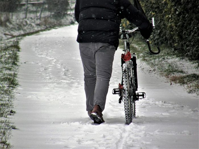 Low Section Of Man With Bicycle Walking On Snow Covered Field