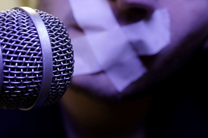 Cropped image of microphone against man with tape on mouth