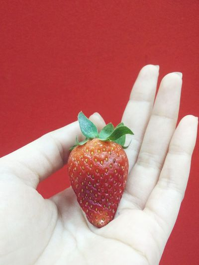 Close-up of hand holding strawberry against red background