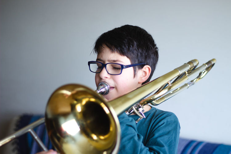 Boy playing trombone at home