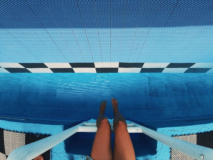 Low section of woman legs in swimming pool