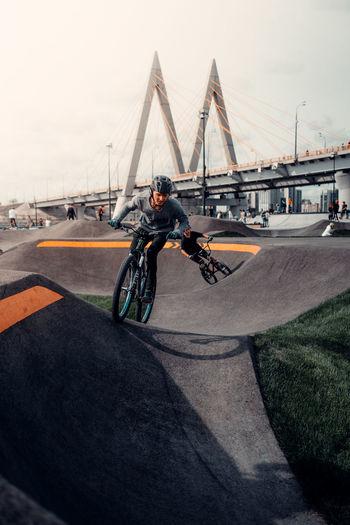 Man riding bicycle on bridge