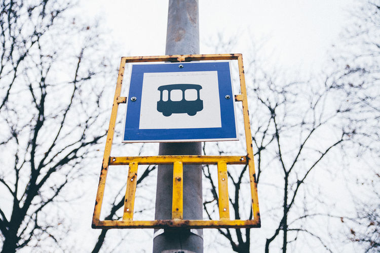 Low Angle View Of Bus Stop Sign On Pole Against Sky