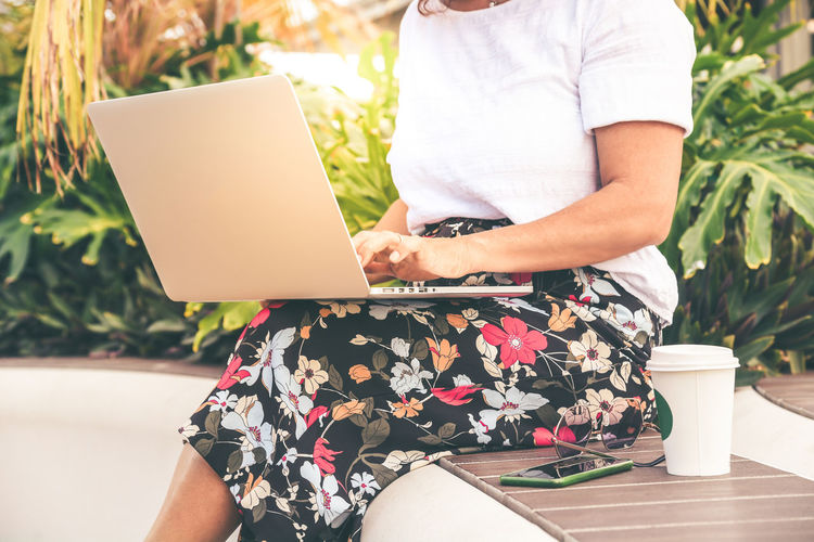Midsection of woman using laptop while sitting against plants