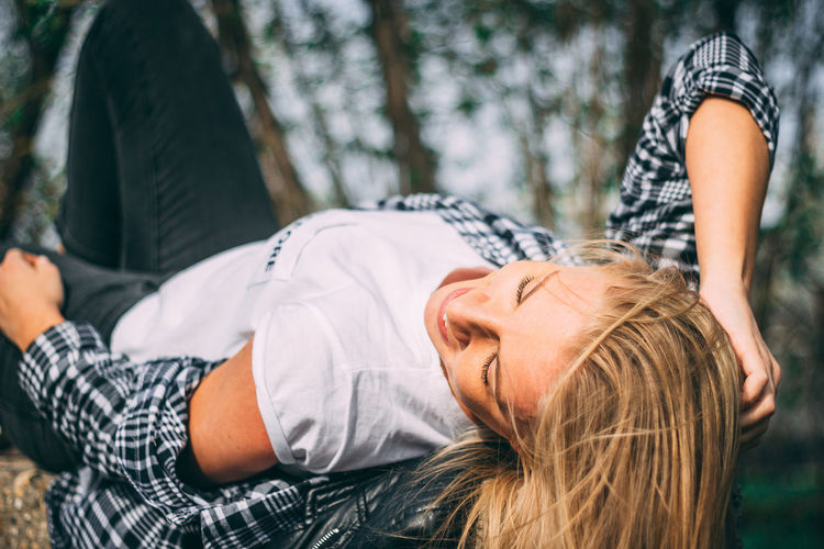 Smiling woman lying in forest