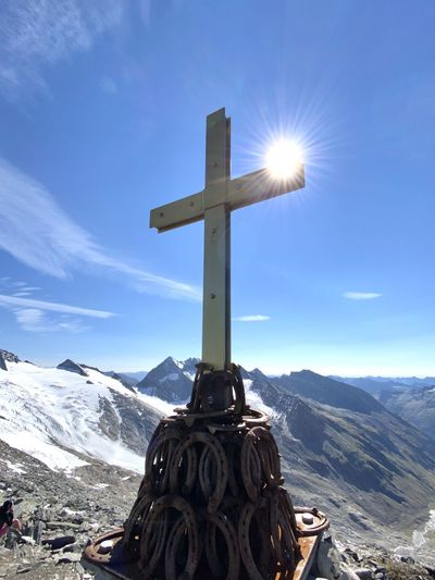 Cross on snowcapped mountains against sky
