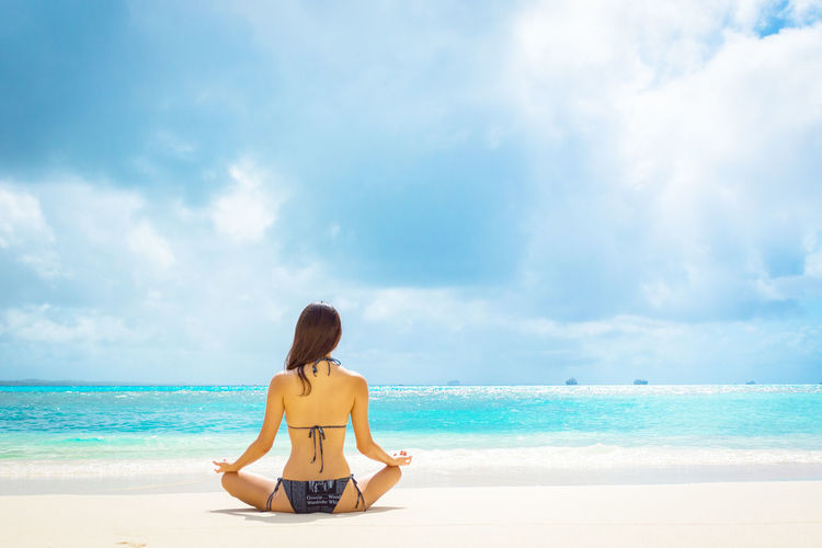 Rear View Of Young Woman Meditating At Beach Against Cloudy Sky During Sunny Day