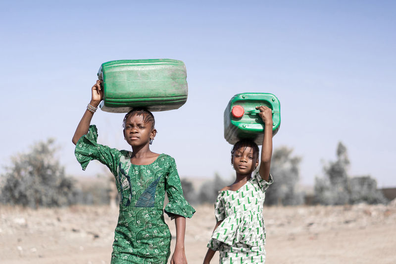 Portrait of girls carrying containers while walking on land