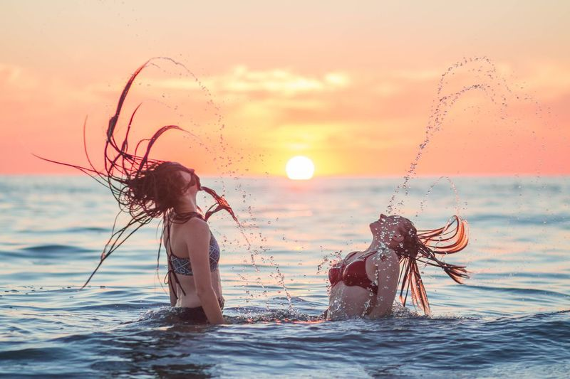 Spread Love EyeEm Selects Sunset Water Splashing Sky Sea Nature Two People Orange Color Motion Leisure Activity Beauty In Nature People Lifestyles Sunlight Women Real People Outdoors Waterfront