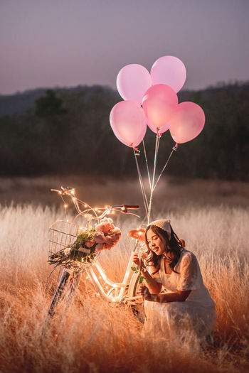 Woman with balloons sitting on illuminated bicycle on field against sky at sunset