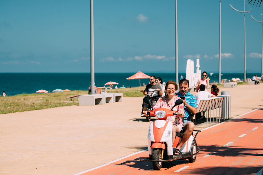 Batumi, Adjara, Georgia - September 9, 2017: People Riding On Scooter Motorcycle On Bicycle Lane In Seafront Promenade City Georgia Motorcycle Press For Progress Promenade Road Scooter Transport Active Adjara Adult Bicycle Lane Men People Riding Sea Seafront Sky Smiling Summer Tourism Vacations Women Young Women This Is Family