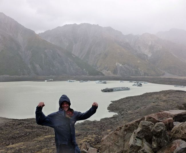 Portrait of happy hiker flexing muscle against lake and mountains during foggy weather